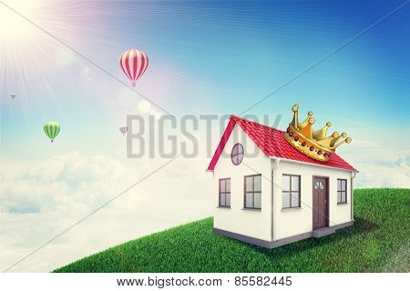 White house with red roof and crown on green grassy hill. Background sun shines brightly, flying hot
