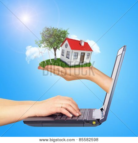 White shack in hand with red roof and chimney of screen laptop.  Background sun shines brightly on l