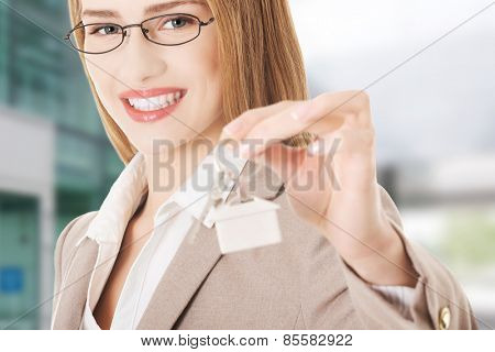 Caucasian business woman holds silver home keys