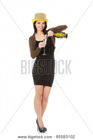 Woman in party dress pours champagne into glass.