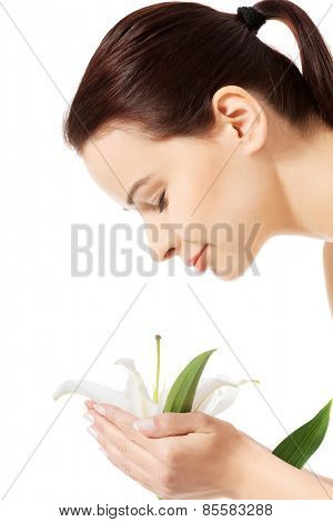 Young woman smelling white lily.
