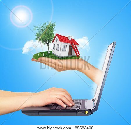 White shack in hand with red roof and chimney of screen laptop. Background sun shines brightly on le