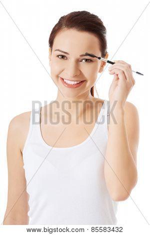 Woman applying make up on her eyebrow.