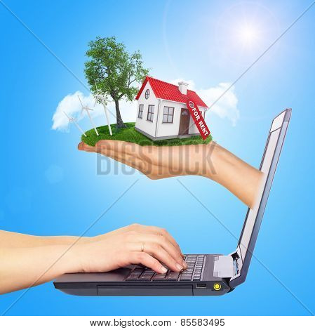 White shack in hand with red roof and chimney of screen laptop. Background sun shines brightly on ri