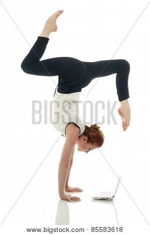 Multitasking. Girl doing handstand with laptop