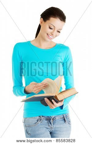 Happy brunette woman reading interesting book.