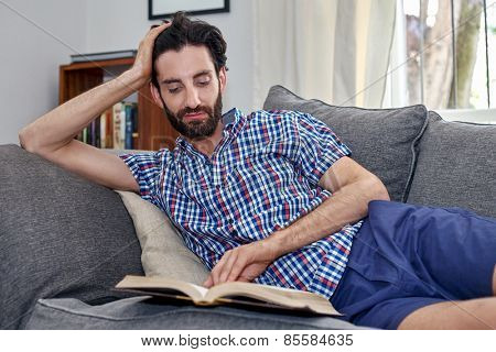 man relaxing on sofa couch reading literature novel story book at home living room lounge