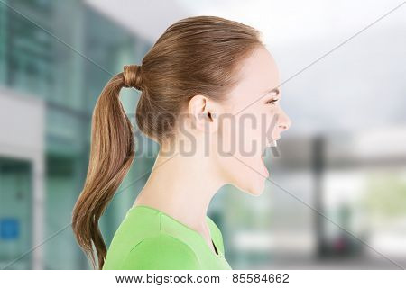 Young casual woman screaming with anger.