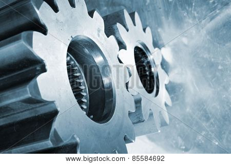 aerospace titanium gears and cogwheels against aluminum background, blue toning.