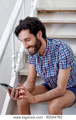 man sitting on staircase with mobile cellphone at home
