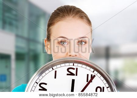 Happy young woman holding office clock.