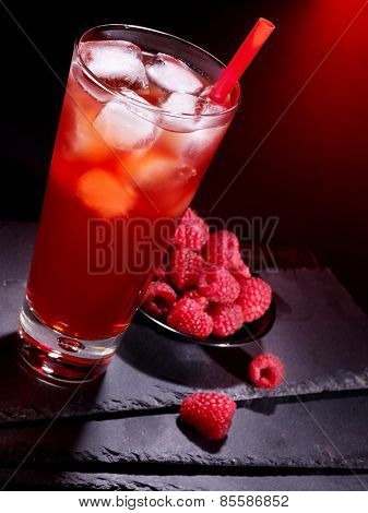 Red raspberry drink  with ice cube on black background.