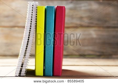 Colorful notebooks and pen on old wooden table