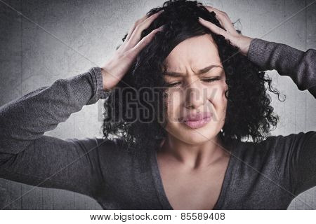 Stressed woman having headache and being despaired, isolated on grey background.