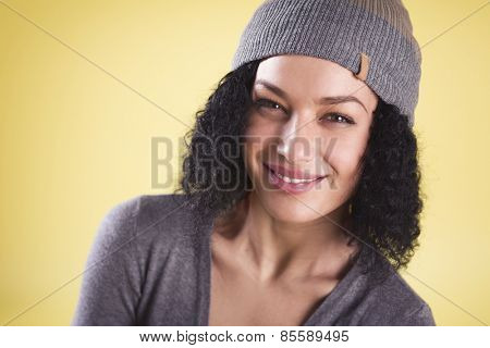 Portrait of a happy cool woman smiling and representing young generation isolated on yellow background with empty copy space.