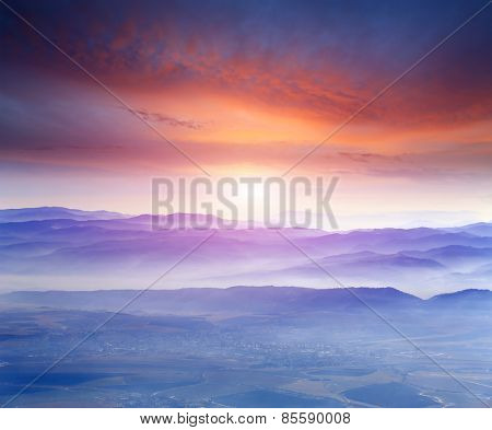 Landscape with sunset over cloudy mountains