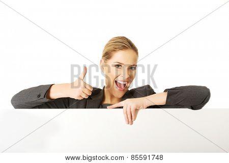 Happy businesswoman holding empty billboard