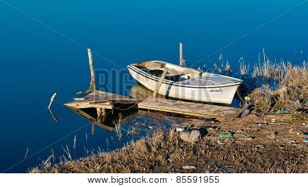 Old Fishing Boat On The Shore. Polluted Environment And Water