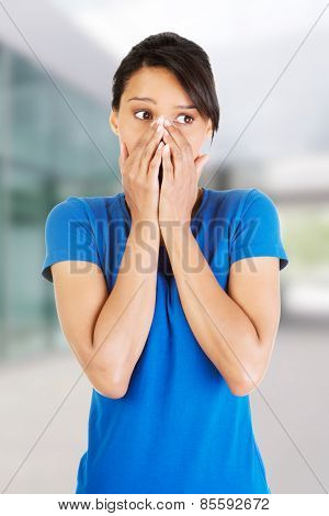 Young scared woman covering the mouth.