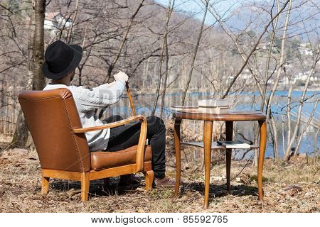 man reading a novel in the woods, rear view