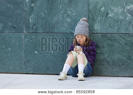little girl sitting with her phone, portrait