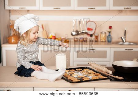 Little cute girl with chef hat preparing cookies in kitchen