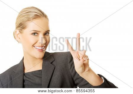 Happy businesswoman showing victory sign.