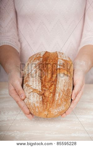 Close up photo of ruddy fresh bread in female hands