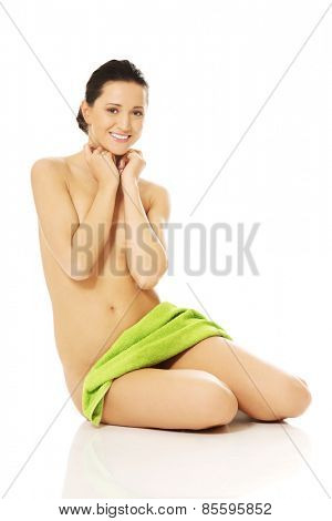 Front view of nude woman sitting, sratching chin and wrapped in towel.