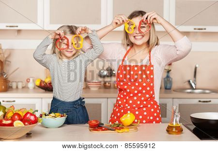 Young mother and her daughter having fun while cooking