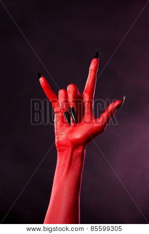 Devil hand showing heavy metal gesture, studio shot on smoky background