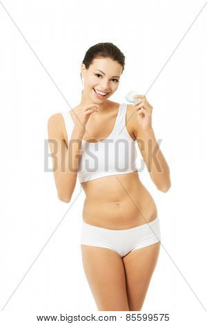 Happy woman holding a dental floss.