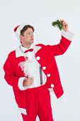 foto of mistletoe  - Geeky hipster in santa costume holding mistletoe on white background - JPG