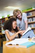 stock photo of classmates  - Student getting help from classmate in library at the university - JPG
