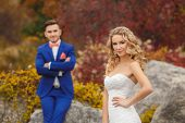 image of blue butterfly  - Groom - a young dark-haired man in a blue suit and pink wedding tie - butterfly and blue-eyed bride - curly blond with long hair and a white wedding dress, posing, hugging in the park. ** Note: Soft Focus at 100%, best at smaller sizes - JPG