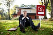 stock photo of house representatives  - Tired estate agent is sitting on grass in front of the house - JPG