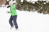picture of snowball-fight  - Young boy in warm winter clothing enjoying a winter snowball fight as he takes aim at the camera with a snowball with standing in pristine white snow with copyspace to the right - JPG