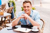 picture of cafe  - Confident young man looking at camera and smiling while sitting in sidewalk cafe - JPG