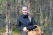 foto of face-fungus  - Young woman with a basket of mushrooms in the forest. Leningrad Region, Russia.