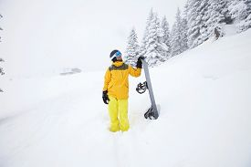foto of snowboarding  - Male snowboarder in yellow sportswear standing with snowboard looking up and planning the route of descent for unknown ski track - JPG