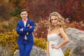 stock photo of tied hair  - Groom - a young dark-haired man in a blue suit and pink wedding tie - butterfly and blue-eyed bride - curly blond with long hair and a white wedding dress, posing, hugging in the park. ** Note: Soft Focus at 100%, best at smaller sizes - JPG