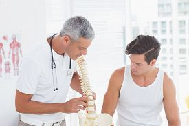 foto of herniated disc  - Doctor showing anatomical spine to his patient in medical office - JPG