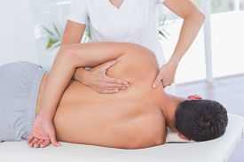 foto of shoulder-blade  - Physiotherapist doing back massage to her patient in medical office - JPG