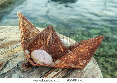 Souvenir boat made of rusty metal wire gauze mesh at sea water background