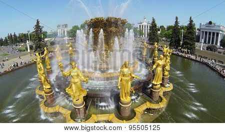 RUSSIA, MOSCOW - MAY 18, 2014: Friendship of Nations fountain on square with many people at All Russia Exhibition Center in spring sunny day. Aerial view