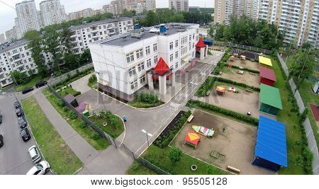RUSSIA, MOSCOW - 28 MAY, 2014: Kindergarten with playgrounds near dwelling houses and car parking at spring day. Aerial view