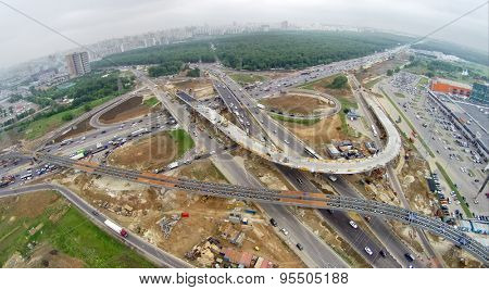 RUSSIA, MOSCOW - MAY 28, 2014: Cityscape with building site of Borovskaya flyover and transport traffic on beltway in spring cloudy day. Aerial view.