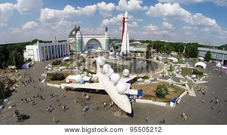 RUSSIA, MOSCOW - MAY 24, 2014: People walk by Industrial Square with monument of aircraft and space rocket at territory of All Russia Exhibition center in spring sunny day. Aerial view