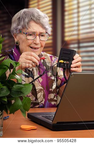 Old woman is trying to install audio video adapter