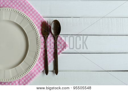 Wooden Spoon And Fork With Dish On White Wooden Table